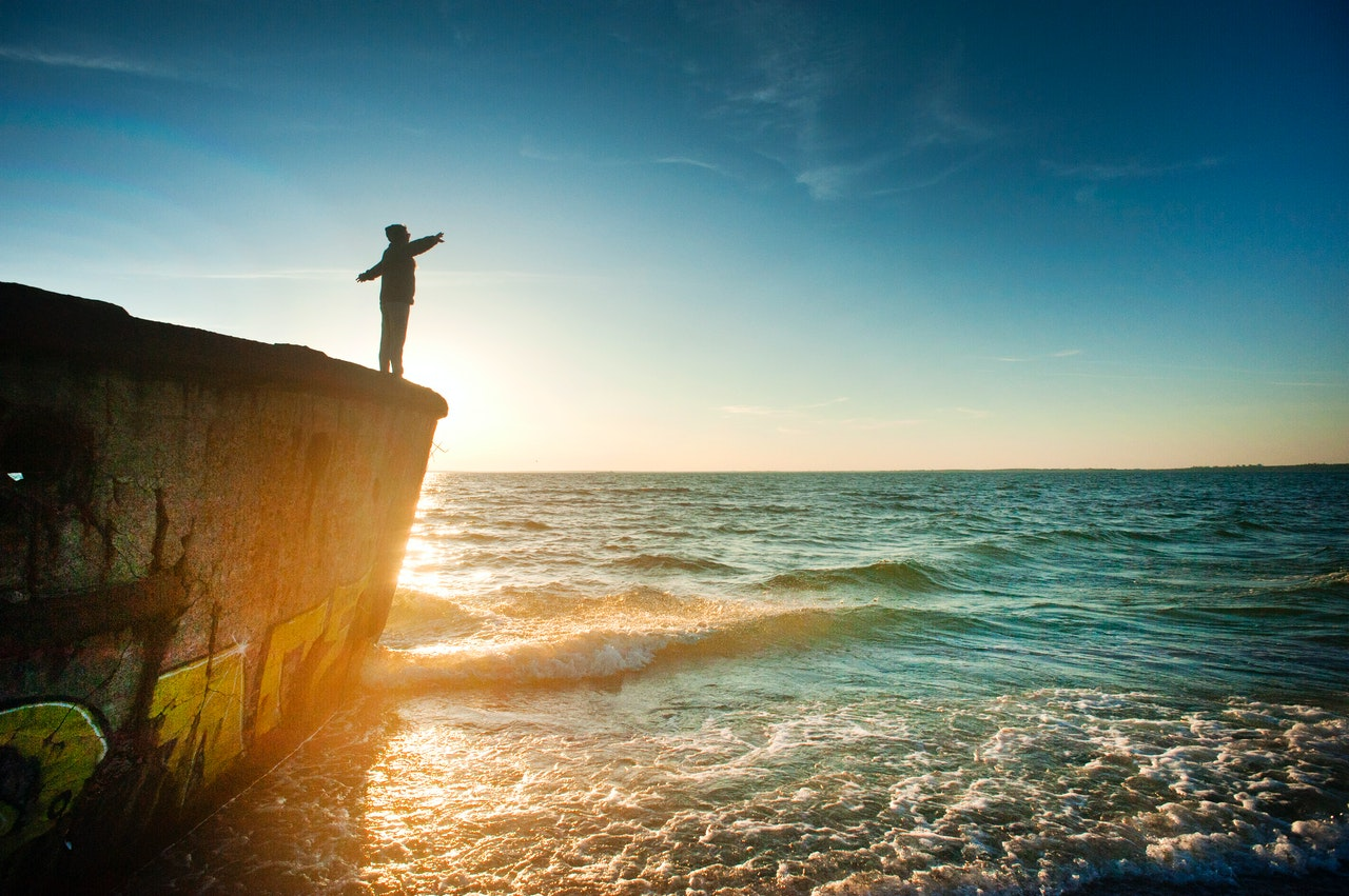 silhouette-of-person-on-cliff-beside-body-of-water-during-1060489(1)